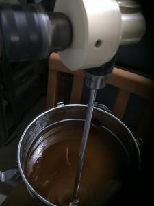 Der Honigrührer im Einsatz. Im Bild oben das Untersetzungsgetriebe, unten der zu rührende Honig.