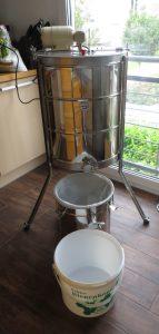 Honigschleuder im Hintergrund, davor Metallgefäß mit einliegendem Feinsieb, davor am Überlauf ein Lebensmitteleimer