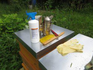 Milchsäure 15% ad us vet. und das Imkerwerkzeug: Kehrbesen, Stockmeißel und Smoker. Davor Schutzhandschuhe für die Säurebehandlung